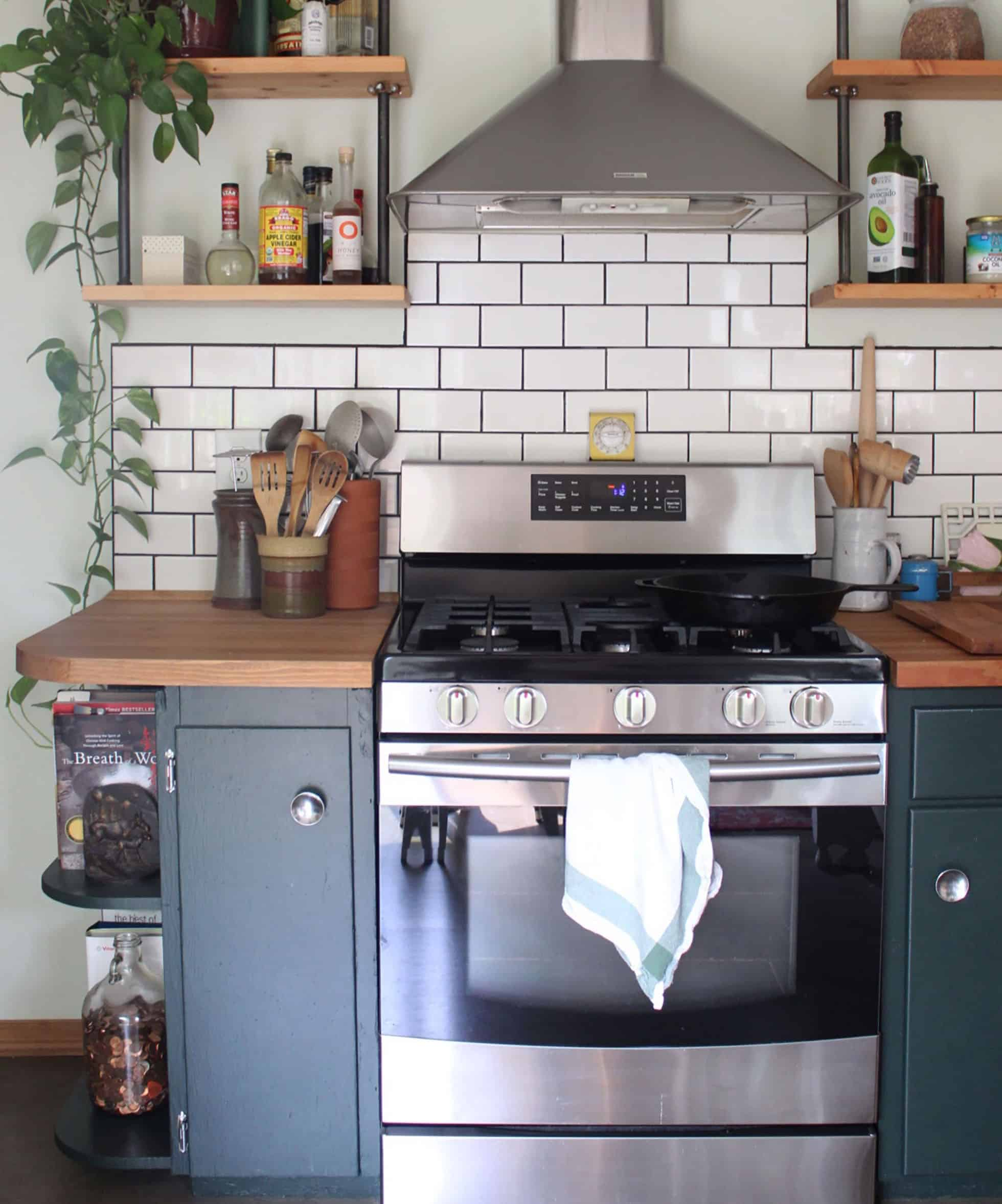 Stainless steel stove with hood between dark blue cabinets