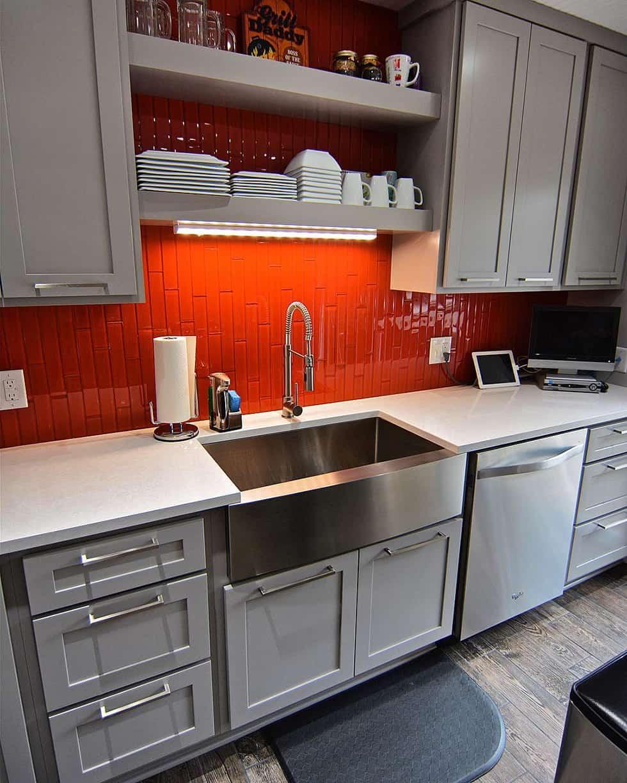 Orange tile backsplash in white kitchen with stainless sink