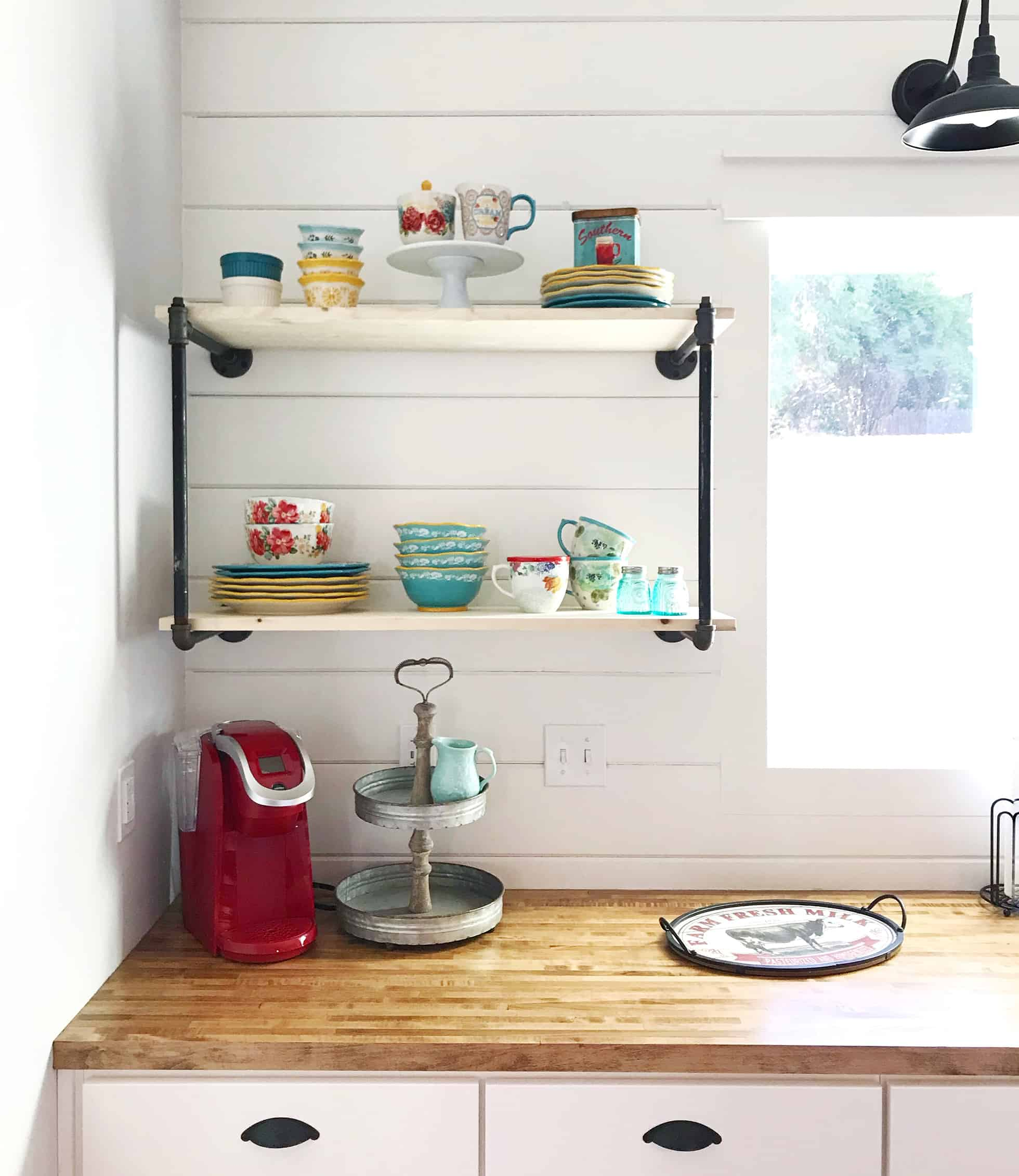 Gas-pipe shelving with vintage china in white kitchen