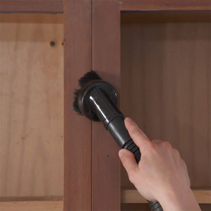 Cleaning sanded cabinets with vacuum.