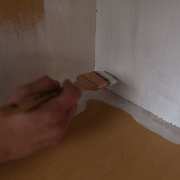 Applying primer to cabinet interiors.